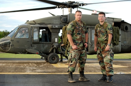 SAN ISIDRO AIR BASE, Dominican Republic -- Air Force Staff Sgts. David Pagani (left) and Robert Daly, Joint Task Force-Bravo Medical Element, with one of the two UH-60 Black Hawk helicopters they helped put together in the Dominican Republic.  JTF-Bravo deployed a team of 21 servicemembers to assist in relief efforts after Tropical Storm Noel pounded the small island nation.  (U.S. Air Force photo by Staff Sgt. Austin M. May)