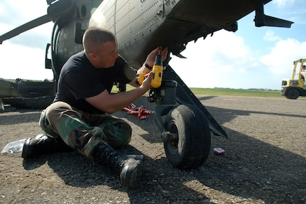 SAN ISIDRO AIR BASE, Dominican Republic -- Air Force Staff Sgt. David Pagani, Joint Task Force-Bravo Medical Element, screws panels onto an Army UH-60 Black Hawk helicopter during a disaster relief mission to the Dominican Republic.  JTF-Bravo deployed a team of 21 servicemembers to assist in relief efforts after Tropical Storm Noel pounded the small island nation.  (U.S. Air Force photo by Staff Sgt. Austin M. May)