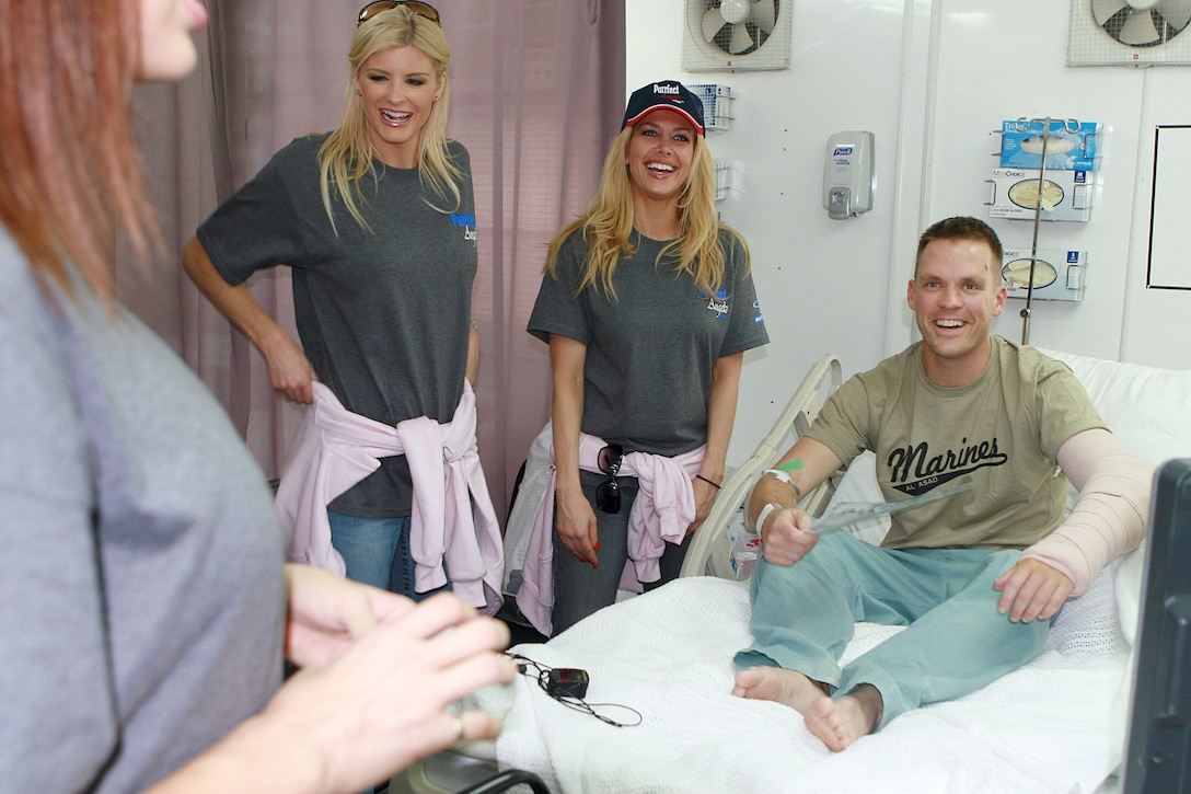 AL ASAD AIR BASE, Iraq, -- The 'Purrfect Angelz' pose with a Marine at the base hospital. The hospital was one of the Angelz' stops on their base tour here Nov. 18. Following the troop visits, the Angelz performed at the Base Theatre for Marines, soldiers, sailors, and airmen of 2nd Marine Air Wing (Fwd). Official Marine Corps Photo By Cpl. Ryan C. Heiser.