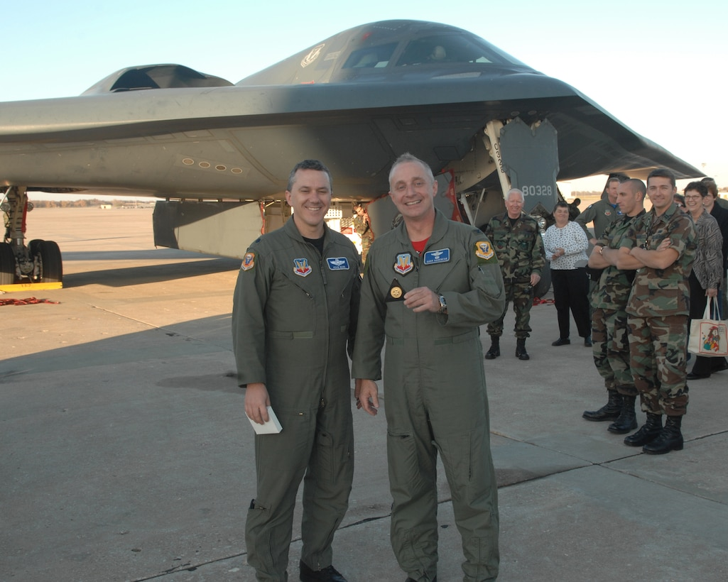 WHITEMAN AIR FORCE BASE, Mo. -- Lt. Col. Kevin Ward, 509th Bomb Wing director of staff and instructor pilot, congratulates Col. Garrett Harencak, 509th BW commander, as the commander holds up his Spirit coin for being the 407th person to fly a B-2. Colonel Harencak took his first B-2 flight in the Spirit of Texas Nov. 9. (U.S. Air Force photo/Airman 1st Class Cory Todd)