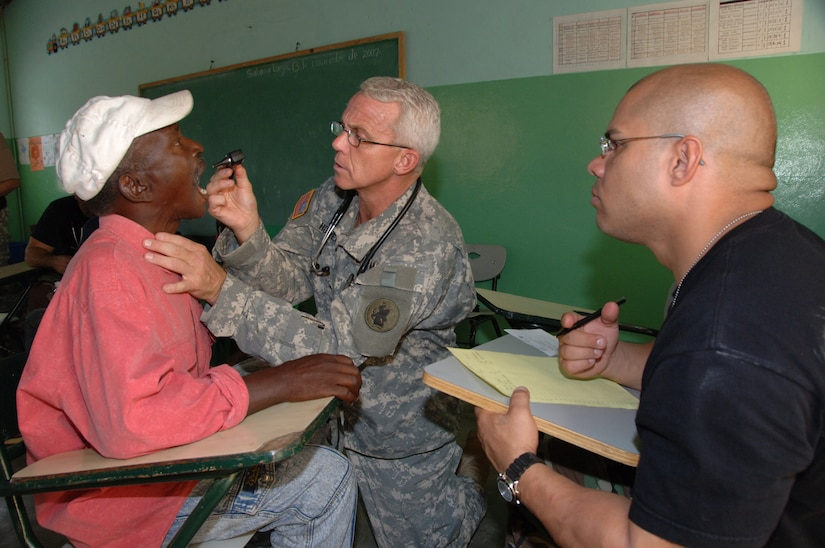 EL LIMONAL, Dominican Republic -- Army Lt. Col. (Dr.) Michael Hoilien, assisted by Air Force Staff Sgt. Luis Santa, examines the throat of a Dominican man at a clinic set up by U.S. servicemembers from Joint Task Force-Bravo Nov. 10. The pair were part of an Expeditionary Medical Liaison Team deployed to the Dominican Republic to provide medical assistance to the island nation. (U.S. Army photo by Juan Torres)
