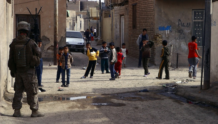 "A Marine with Company K, 3rd Battalion, 5th Marine Regiment, Regimental Combat Team 6, posts as security and watches as neighborhood children crowd the streets around him, Nov. 18. The Marines with Co. K regularly handed out school supplies in the area over the past months to encourage the children to attend school. ""After being here a month and a half, I've noticed that a lot more kids are going to school now,"" said 28-year-old Sgt. Ysac M. Perez, a squad leader with 4th platoon."