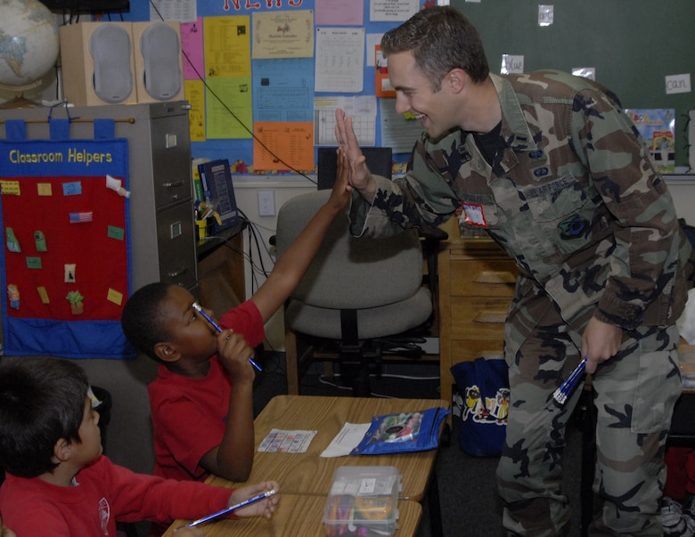 Lt. James Spindler, Satellite Control and Network Group, gives a student at St. Jerome's Catholic School in Westchester a high five. Approximately 20 military members, including ten Air Force personnel, spoke to students about their military career and the importance of education. The service members were recognized as a group at a school assembly. (Photo by Joe Juarez)