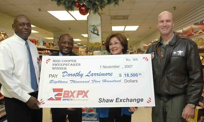SHAW AIR FORCE BASE, S.C. -- Jonathan Bright, Army Air Force Exchange Service store manager, Maurice Joiner, AAFES general manager, and Col. James Post, 20th Fighter Wing commander, present a check for $18,500 to Mrs. Dorothy Larrimore Nov 16. Mrs. Larrimore won the Sobe Mini Cooper Sweepstakes sponsored by Pepsi Cola and AAFES. (U.S. Air Force photo/Airman 1st Class William Coleman)
