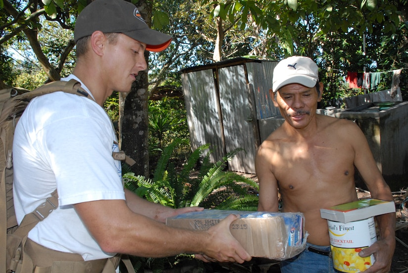 LA SAMPEDRANA, Honduras - Air Force 1st Lt. Timothy Brodman delivers food to a local Honduran man here during a mountain hike.  Airman, Soldiers and Sailors from Joint Task Force-Bravo at Soto Cano Air Base, Honduras, hiked five and a half miles up the mountain here to deliver more than 600 pounds of food to local villagers.  This hike is the third in a series of five sponsored by the JTF-Bravo Chapel. (U.S. Air Force photo/Tech. Sgt. Sonny Cohrs)