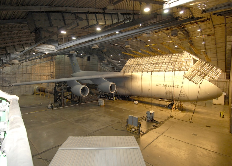 EGLIN AIR FORCE BASE, Fla. -- The C-5M Super Galaxy undergoes extreme heat and ultraviolet exposure during the Re-engining and Reliability Program at the McKinley Climactic Laboratory Oct. 21 through Nov. 17. Some of the unique challenges the laboratory crew faced was getting the C-5M inside the hangar. Some of the hangar piping hung lower than the C-5 tail creating an obstacle for the crew moving it inside the hangar. They needed to lower the tail-end of the airplane within inches of touching the ground and jacked up the front-end in order to get the right leverage. Because the airplane's size, the solar panels had to be constructed after the C-5 was loaded rather than have everything pre-constructed. (Photo by Greg Murry)
