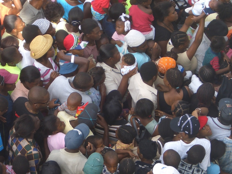 PORT AU PRINCE, Haiti -- Thousands of Haitians push to be seen by U.S. medical workers in August.  Children were held high above the crowd to avoid suffocation.  (U.S. Air Force/courtesy photo)