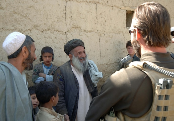 An Air Force Office of Special Investigations agent speaks with villagers during a medical engagement mission here. Special agents assigned to the AFOSI Expeditionary Detachment 2405 here regularly work together with Afghan National Police on a broad range of missions related to humanitarian assistance and security.(U.S. Air Force photo by Staff Sgt. Mike Andriacco)