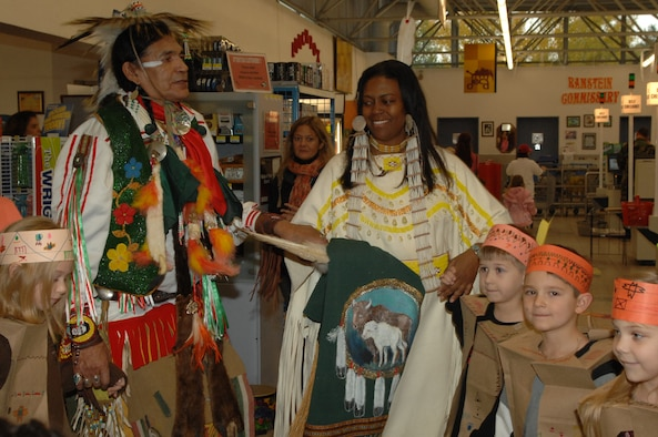 James Shepherd (left) and Andrea La boy do a round dance with the second and third graders from the Ramstein Elementary School for the kick-off of Native American Heritage Month Nov. 7 at the Ramstein commissary. (U.S. Air Force photo/Airman 1st Class Amber Bressler)