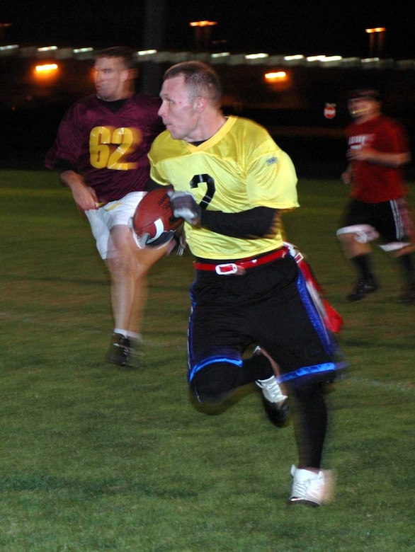 Max Briggs, Travis Red All-Stars' quarterback, evades defenders on his way to a 25-yard gain during the Intramural Flag Football All-Star Classic Nov. 20.  Briggs threw for 100 yards, two touchdowns and had three interceptions. The Red All-Stars defeated the Gold All-Stars 14-12. (U.S. Air Force photo/Staff Sgt. Candy Knight)