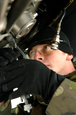 Airman 1st Class Steve Wilson, 28th Aircraft Maintenance Squadron, endures the cold temperatures as he cuts the safety wire on the flame holder inside one of the B-1's engines.  (U.S. Air Force photo by Staff Sgt. Michael B. Keller)