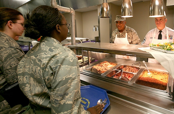 The 37th Training Wing command chief master sergeant and the director of staff, Chief Master Sgt. Dwayne Hopkins, right, and Col. Stevenson Ray, respectively, serve a Thanksgiving meal to trainees at the 322nd Training Squadron on Thanksgiving Day. Chief Hopkins and Colonel Ray were two of more than 80 members of Team Lackland who worked shifts in eight open dining facilities on Thanksgiving. (USAF photo by Robbin Cresswell)