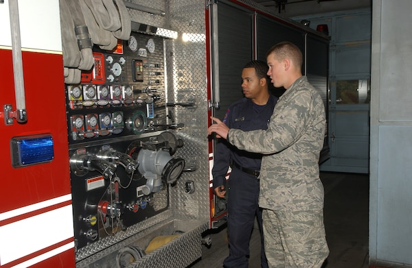Trainee Michael Nieman, 320th Training Squadron, gets a personal tour of Engine 19 at fire station 19 on Vance Jackson Road by firefighter Joe Brown. Trainee Nieman was one of 20 basic trainees adopted by 10 area fire stations on Thanksgiving Day as part of Operation Homecooking. (USAF photo by Alan Boedeker)