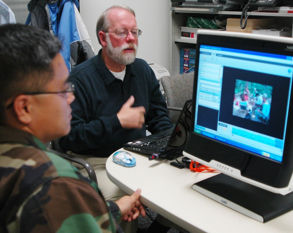 Rob Daves, The Everett Group, director of national studies, conducts an eye-tracking test with Capt. Brian Grocki, 2nd Space Warning Squadron, to see which parts of a photo draw his attention. The Everett Group was contracted to determine how people who access www.af.mil and the Air Force Portal navigate the sites and what changes could be made to make the sites more user friendly. (Photo by Staff Sgt. Scott McNabb)