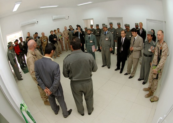 Brig. Gen. Sayed Ahmad Nasir Hashimi (center, in gray), the director of information communication technology for the Ministry of Information, speaks to a group of MoI personnel, contractors and representatives from Afghan Wireless Communications Company and Combined Security Transition Command-Afghanistan during the opening of a new network operations center at MoI headquarters. The new center will improve both internal and external communications for the MoI and the computer network for the headquarters.  (U.S. Navy Photo/ Petty Officer First Class David M. Votroubek)