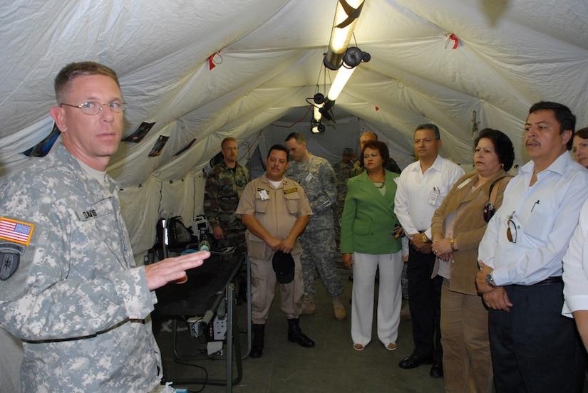 SOTO CANO AIR BASE, Honduras -- Army Maj. (Dr.) Kurt Davis, a general surgeon and Mobile Surgical Team commander, explains field medical procedures to a group of Honduran government officials during Local Leaders Day here Nov. 27.  The annual event brought together not only Honduran government leaders, but also representatives from the U.S. Embassy, World Food Program, and the U.S. Agency for International Development.  (U.S. Air Force photo/Tech. Sgt. Sonny Cohrs)