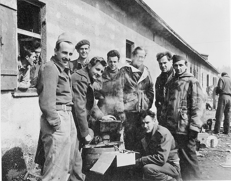 "Charles Woehrle is included in a group photo taken at  at Stalag VII A Moosburg, Germany. Pictured are (L-R) John Fitzpatrick (hand in pocket), Ed Stephenson (beret), Ernie Sands (bending over stove), Francis ""Fran"" Finnegan, John Lindquist,Woehrle, Jim Houser and Lt. Marshall Draper (kneeling) of the 15th Bombardment Squadron. Draper had the unfortunate distinction to be the first U.S. POW in Germany, shot down on 21 June 1942.  Lindquist and Houser are wearing German reversible padded parkas, probably gathered as ""war booty"". These men were roommates at Stalag Luft III, South Compound, Block 130, Room 10. They kept together on the march in January 1945, sharing food and emotional support.  (Photo courtesy of Ben van Drogenbroek through the 458th Bombardment Group (H) Web page, www.485bg.com.)"