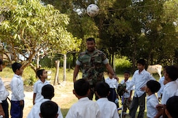 Sihanoukville, Kingdom of Cambodia (Nov. 29, 2007) - Culinary Specialist 1st Class (SW/AW) Rosco Cohen, and assigned to Amphibious Squadron Eleven, plays soccer with the students from the Chamka Kaosu school during a community relations project, Nov. 29.  Essex and the embarked 31st MEU arrived in Sihanoukville, Kingdom of Cambodia, Nov. 26, for a scheduled port visit that gives Sailors and Marines the opportunity to participate in friendship-building community relations events, medical and dental projects and professional exchanges.  These friendship-building events are being conducted with the cooperation of the Cambodian military and the Kingdom of Cambodia.  The visit also provides Sailors and Marines the opportunity to meet local citizens and experience the customs and traditions of the Cambodian people.  Essex is the lead ship of the only forward-deployed U.S. Expeditionary Strike Group and serves as the flagship for CTF 76, the Navyâ??s only forward-deployed amphibious force commander.  Task Force 76 is headquartered at White Beach Naval Facility, Okinawa, Japan, with a detachment in Sasebo, Japan.  U.S. Navy photo by Mass Communication Specialist 1st Class (AW) Jeffrey Ballge