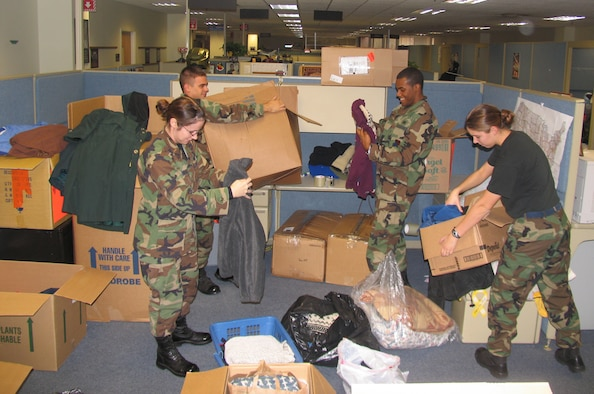 HANSCOM AFB, Mass. -- Hanscom lieutenants (from left) Holly Chernushin, 66th Comptroller Squadron, Josh Neustrom, 851st Electronic Systems Group, Karl Artis III, 66th Mission Support Squadron, and Felisa Dyrud, 66 MSS, sort and pack donated clothing items and blankets on Nov. 28. The clothes and blankets will be sent to Afghanistan and distributed to poor people living there. The lieutenants organized the clothing and blanket drive, which resulted in more than a dozen boxes of donated items, days before the Thanksgiving holiday as a means for Hanscom personnel to share their wealth with those less fortunate. (U.S. Air Force photo by 1st Lt. Lisa Spilinek)
