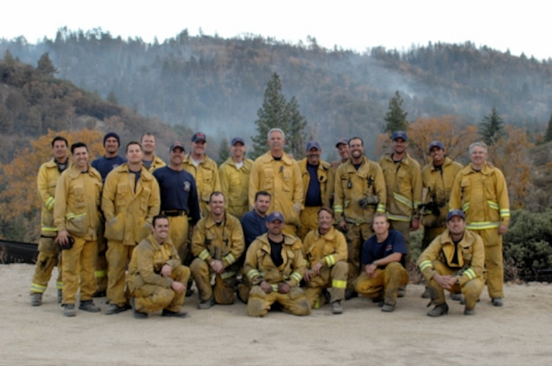 At the end of one of their workdays at the recent Lake Arrowhead fire, the whole Strike Team (1203A) and additional crew from Burbank, Glendale, Pasadena and Alhambra take a well- deserved break as the fire continues to burn the background.  Captain Hultgren is second from the left squatting in the bottom row.