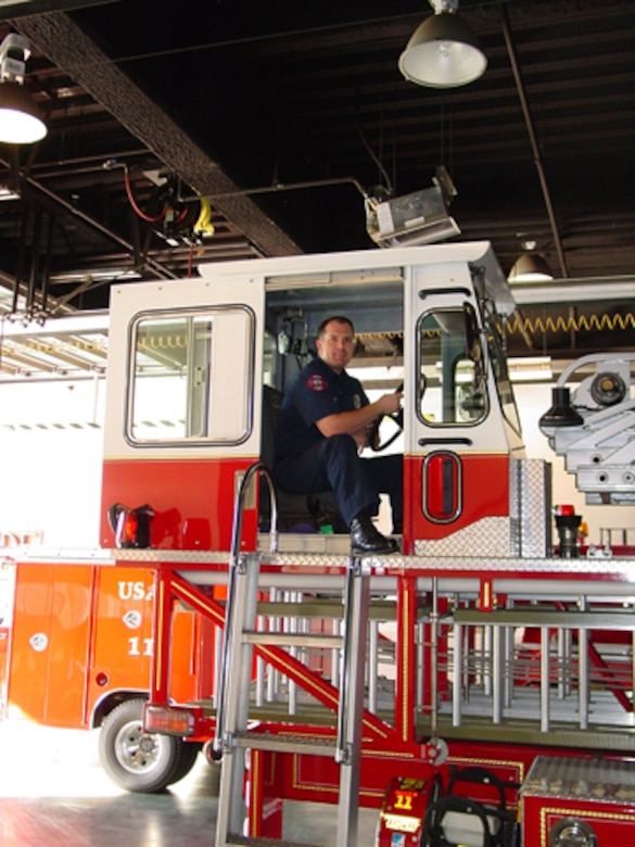 "Burbank firefighter and Air Force Reserve Capt. Ken Hultgren sits up in the Tillerman's Position on the Aerial Ladder Truck.  Captain Hultgren calls it ""the best spot on the job.  I get to drive the back of the truck."""