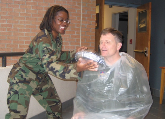Senior Airman Hazel Butler, 14th Operations Support Squadron, serves a pie to Col. Jeff Dunn, 14th Flying Training Wing vice commander, Tuesday. Colonel Dunn was the lucky recipient of a pie due to the pie-in-the-face contest held by the Airman's Activity Council. Sonic Johnson, 14th FTW Public Affairs, and Diane Clardy, 14th FTW Protocol, also received pies Tuesday. (U.S. Air Force photo by Airman 1st Class Danielle Powell)