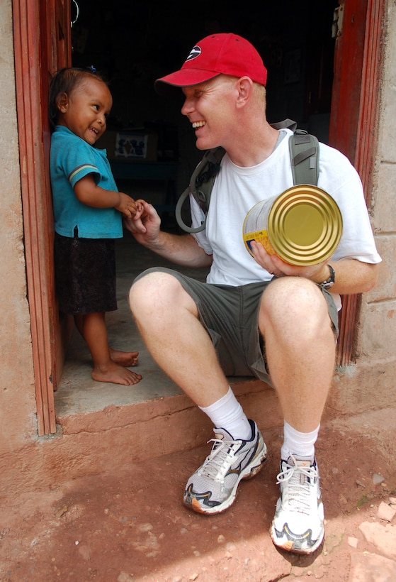 MATA DE PLATANO, Honduras -- Air Force Chaplain (Capt.) Chad Bellamy, Joint Task Force-Bravo chaplain, plays with a young Honduran girl during a break on a nearly five-mile hike to deliver the supplies to families living in the mountains.     (U.S. Air Force photo by Staff Sgt. Austin M. May)