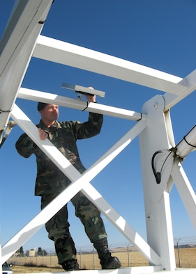 "FAIRCHILD AIR FORCE BASE, Wash. – Tech. Segt. Dan Merrill, Fairchild NCO-in-charge of the Installation Security Constable program, checks the bars on the ""Sky Watch"" tower, a mobile surveillance tower, prior to positioning it. (U.S. Air Force photo/Shadi May)"
