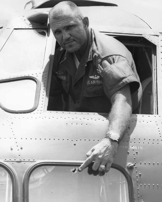 Maj. Ralph Dresser pointing to a bullet hole in a window dangerously near the pilot's seat on a C-123B. (U.S. Air Force photo)