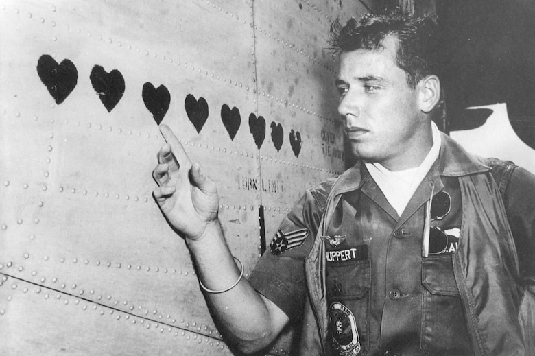 Many Ranch Hand personnel received Purple Hearts for wounds in action. They also recorded them as hearts on the side of their aircraft. Here, A1C Michael L. Shuppert points to his on the C-123 named Leper Colony. (U.S. Air Force photo)