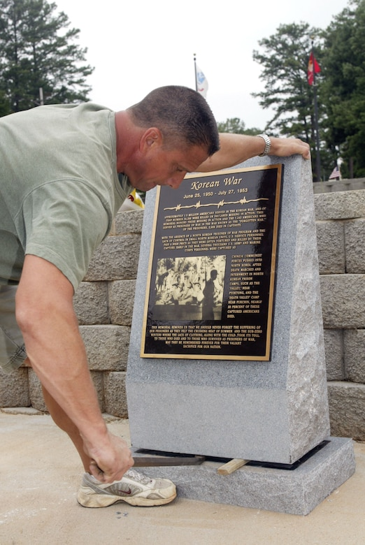 A volunteer works at installing the new Korean War memorial at the Dobbins POW/MIA park. The installation took place directly after the living memorial ceremony and tree planting. The monument is one of four planned for the park. (U.S. Air Force photo/Don Peek)