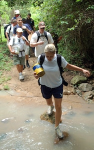 Staff Sgt. Melinda Atencio leads a group of military members across a stream during a hike to deliver food Sept. 29 to a village in the mountains near Comayagua, Honduras. The hike was sponsored by the Joint Task Force-Bravo Chapel from Soto Cano Air Base, and consisted of 55 volunteers who delivered approximately 450 pounds of supplies. (U.S. Air Force photo/Staff Sgt. Austin May)