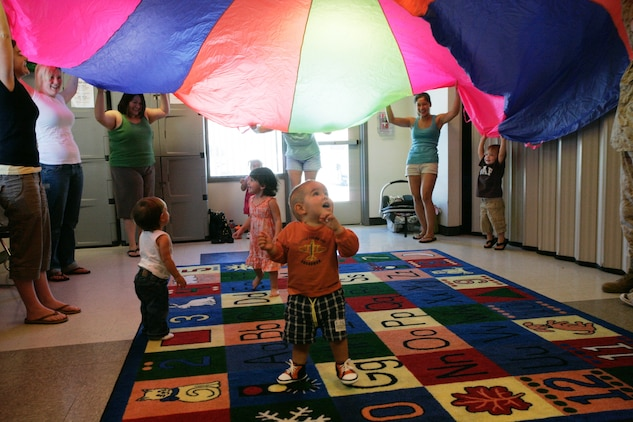 With the help of parents, Levi Free, Lily Ledbetter and Olivia Garansvay, rush under the parachute in excitement during a Kindermusik class Wednesday.