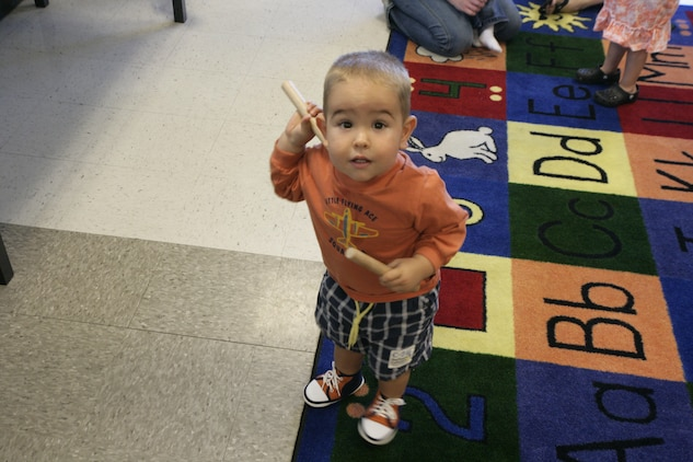 Levi Free, 18 months, plays with rhythm sticks during a kindermusik class Wednesday. The rhythm sticks help the children develop their motor skills and a steady musical beat.