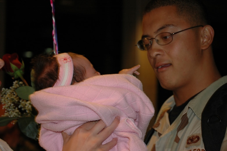HILL AIR FORCE BASE, Utah-- Senior Airman Calvin Miranda, 75th Security Forces Squadron, holds his two-month old daughter for the first time since returning from Iraq Oct. 2.  The 45 Airmen returned from a seven month deployment to Iraq. (U.S. Air Force photo by Capt. Genieve David)