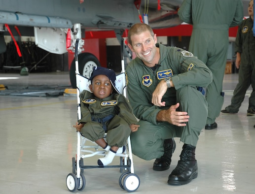 Lt. Col. Kevin Huyck, 95th Figther Squadron commander explores an F-15 with C.J. a participant in the Pilot for a Day program here Tuesday