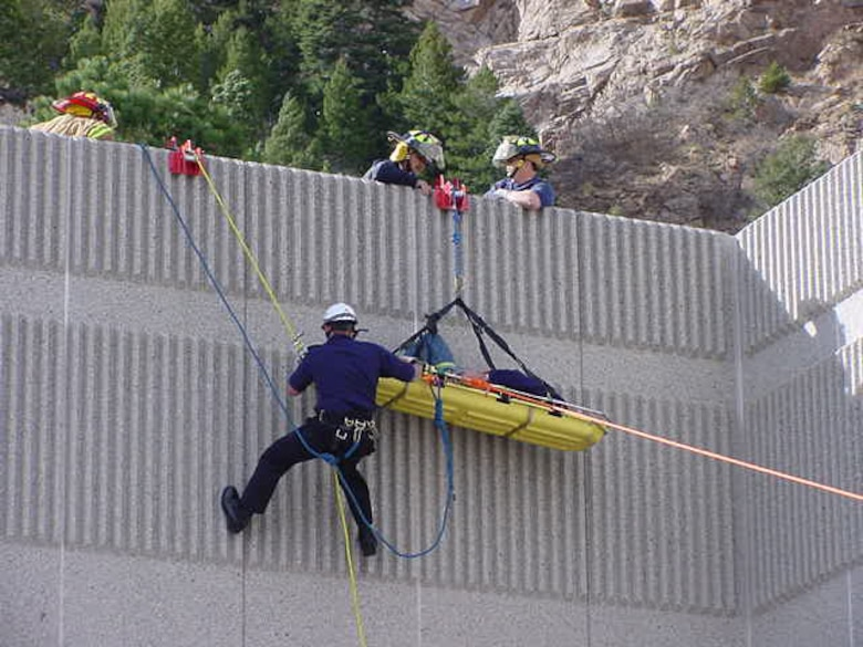Firefighters at Cheyenne Mountain AFS rescue a man with a broken hip off the roof of a building. The man broke his hip while working on the roof in winds up to 75 mph. Cheyenne Mountain's fire department often responds to calls related to the mountain's erratic weather, from high winds to large snow storms. (U.S. Air Force photo)