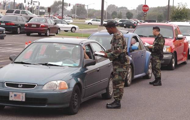 Two 72nd Security Forces Squadron members ticket a line of vehicles during a safety spot check Sept. 26 at the base exchange parking lot. (Air Force photo by Brandice J. Armstrong)