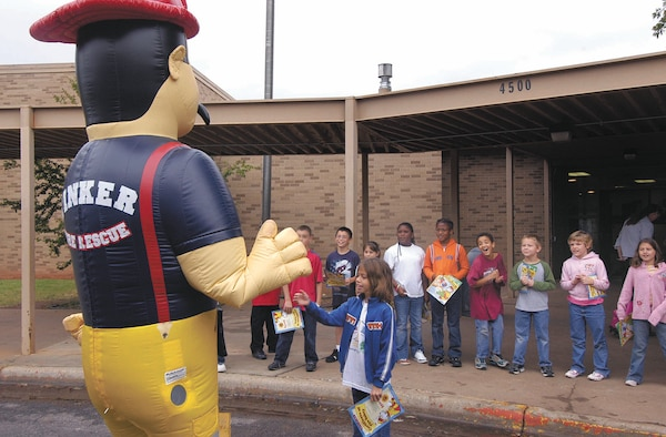 Big Kev waves to Tinker Elementary School students during a previous year's Fire Prevention Week. This year's activities include evacuation drills across base as well as the new Sparky's House, a modified base housing residence used to teach kids how to escape house fires. (Air Force photo by Margo Wright)