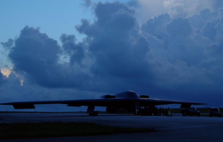 The B-2 Spirits from Whiteman Air Force Base, Mo., arrive here under cloudy skies and a rainy evening 7 Oct. This stealth bomber is parked on the tarmac at Andersen Air Force Base and is immediately serviced by maintenance crews after its arrival. The Spirit is a two-person aircraft and is equipped with stealth technology. These airframes are replacing the B-52 Stratofortresses deployed here from Barksdale Air Force Base, La. (Air Force Photo/Capt. Bryan Florio)