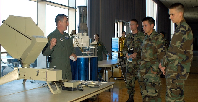 U.S. AIR FORCE ACADEMY, Colo. -- Capt. Denton East explains to freshman cadets here how Milstar's secure satellite communications benefits warriors on the ground during Space Awareness Day here Oct. 6. Captain East's exhibit is a portable satellite communications system that uses Milstar. Captain East is assigned to the 4th Space Operations Squadron at Schriever Air Force Base, Colo. (U.S. Air Force photo/Staff Sgt. Don Branum)