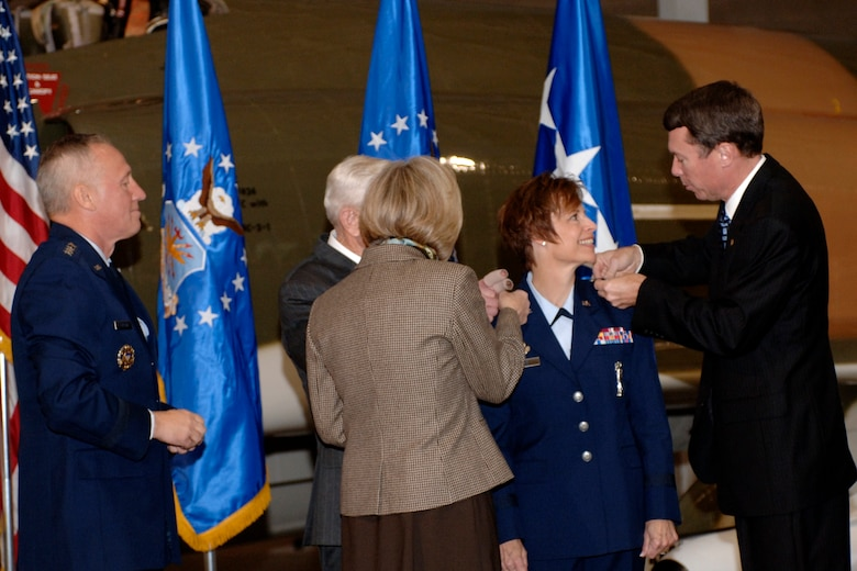HILL AIR FORCE BASE, Utah-- Newly promoted Maj. Gen. Kathleen Close gets her second-star pinned on by her husband retired Col. Mike Close, her sister Patricia Balph, and her godfather retired Col. Patrick Kenny. (U.S. Air Force photo by Todd Cromar)