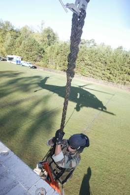 A pararescueman from the 301st Rescue Squadron at Patrick AFB, Fla., lowers himself out the side of an HH-60 Pavehawk during a tactical rescue display at Etowah High School in Woodstock, Ga. Oct. 10. The drop-in was part of Air Force Week Atlanta. Students were also treated to static displays from units at Dobbins Air Reserve Base, Ga., as well as a performance from the Air Force Honor Guard Drill Team. (U.S. Air Force photo/Don Peek)