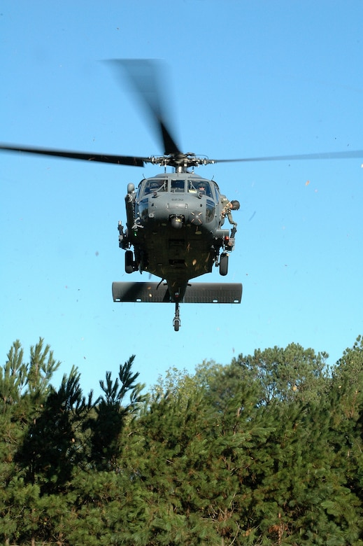 An HH-60 Pavehawk helicopter from the 301st Rescue Squadron at Patrick AFB, Fla., negotiates the treetops at Etowah High School in Woodstock, Ga. The chopper carried pararescuemen who visited the school and performed a display of tactics as part of Air Force Week Atlanta. Students at the school were also treated to several static displays from the 94th Airlift Wing at Dobbins Air Reserve Base, Ga., and a performance of the Air Force Honor Guard drill team with their skill-heavy drill that had jaws on the floor. (U.S. Air Force photo/Micah Garbarino)