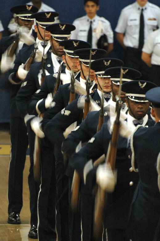 """Members of the Air Force Honor Guard Drill Team perform a """"domino"""" maneuver during a fantastic drill routine at Etowah High School in Woodstock, Ga. Oct 10. The team was part of a large group of Air Force members, active and reserve, who descended on the school to share their story during Air Force Week Atlanta. Students at Etowah were not only treated to a drill performance, but also to a helicopter landing and a demonstration of tactics from members of the 301st Rescue Squadron, Patrick AFB, Fla. and several static displays from the 94th Airlift Wing at Dobbins Air Reserve Base, Ga. (U.S. Air Force photo/Micah Garbarino)"""