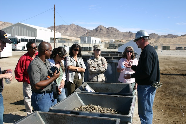 Mike Quintana, supervisor athe the recycling and hazardous waste munitions plant, explains the process of collecting, crushing, organizing and reusing ammunition casings to sponors during the annual MCCS Sponsorship tour Oct. 12.