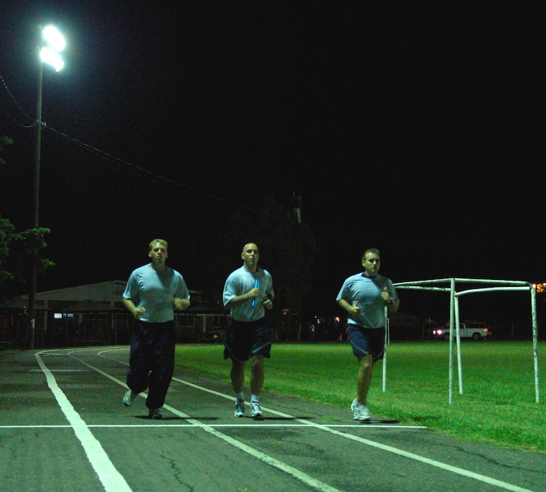 SOTO CANO AIR BASE, Honduras – A few minutes after midnight Oct. 12, Air Force Staff Sgts. Christopher Evans and Jason Caswell, along with Air Force Tech. Sgt. Brandon Williford, keep the 24-hour Prisoner of War/Missing in Action Remembrance Run going through the night.  A total of approximately 170 participants ran in mostly 15-minute intervals for 24 hours to show support for their fellow servicemembers who have been listed as POW/MIA.  (U.S. Air Force photo by Staff Sgt. Austin M. May)
