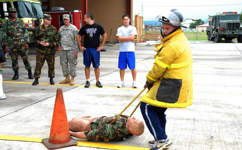 SOTO CANO AIR BASE, Honduras - Army 2nd Lt. Miles Hamlett, Joint Task Force Bravo Medical Element, weaves through cones dragging a mannequin in the Fire Department's Fire Muster Challenge here Oct. 12.  The relay challenge was Soto Cano Fire Department's closing event for Fire Prevention Week.  (U.S. Air Force photo by 1st Lt. Erika Yepsen)