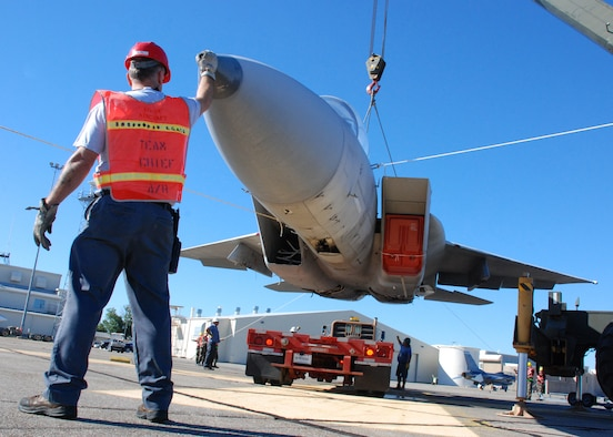 EGLIN AIR FORCE, Fla. --  Dennis Schlitter, DynCorp Aero-repair, helps position the hovering F-15 as a driver backs the flatbed trailer underneath it for transport to an Eglin range Oct. 12. Indyne Inc. U.S. Targets and the 46th Test Wing is moving a F-15 to Range 52 for future testing missions. The crew, lifted the aircraft, collapsed the landing gear and hoisted it onto a flatbed trailer to be transported to Range 52 off Range Road 213. They are scheduled to move the jet beginning at 2 a.m. Oct. 13. (U.S Air Force Photo by Staff Sgt. Mike Meares)