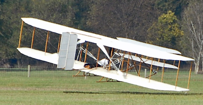 Mark Dusenberry pilots a replica Wright Flyer III he built over Huffman Prairie at Wright-Patterson Air Force Base on Oct. 5.  Dusenberry was reenacting a record breaking flight at the same location 102 years earlier, when Wilbur Wright circled the field for 39 minutes. Dusenberry clipped a wing during a turn about 40 seconds into his flight, damaging both propellers and the undercarriage.  Dusenberry was unhurt and said he plans to repair the aircraft to fly again.  (Skywrighter photo by Christy Web)